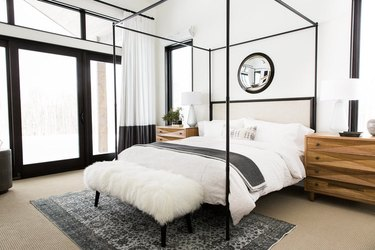 neutral bedroom idea with black canopy bed and black door and window trim