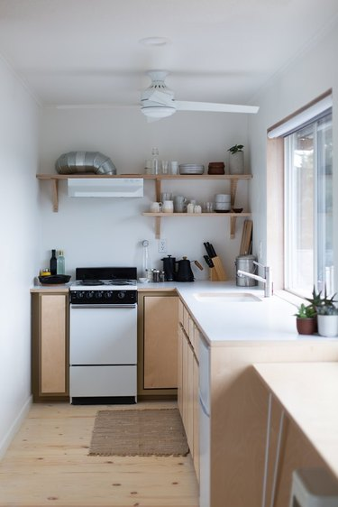 small well-organized kitchen with ceiling fan and large window