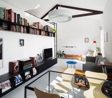open concept living and dining area with floating book shelf