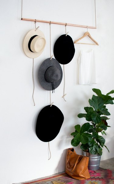 Hats hanging from a copper pipe