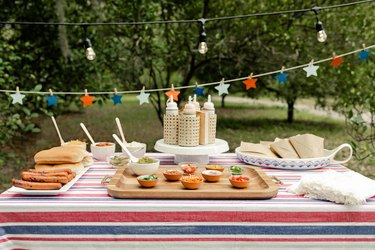 Gourmet hot dog bar with red, white and blue tablecloth, star garland, and small bowls of toppings