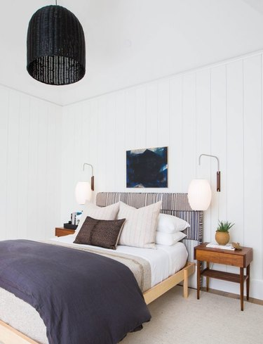 neutral bedroom idea with black pendant and upholstered headboard
