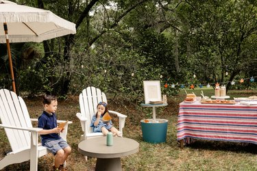 Two small kids sitting in white Adirondack chairs under fringed umbrella enjoying potato chips