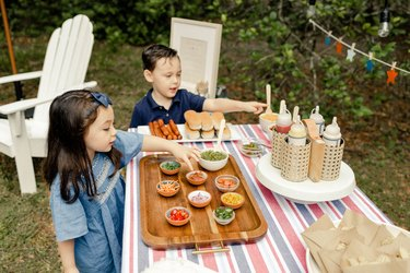 Two small kids pointing to toppings on the hot dog bar table