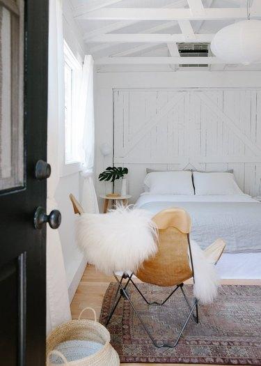 black front door opening to minimal boho bedroom