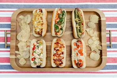 Six gourmet hot dogs plated on wooden serving tray with potato chips