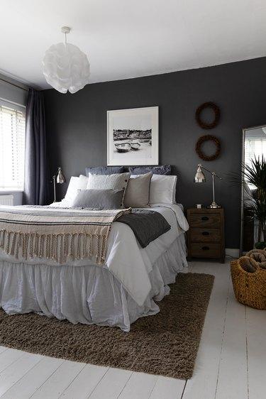 neutral bedroom idea with dark gray walls and drapery