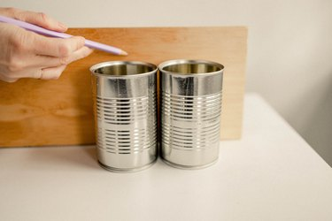 Marking height of empty soup cans on wood board