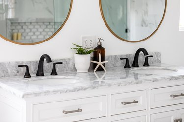 white vanity with gray marble countertop, double sinks with black faucet, vase with green plant, starfish decoration, soap dispenser, two round mirrors with gold trim