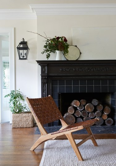 traditional mantel decor with ornate black tiled fireplace and wood side chair