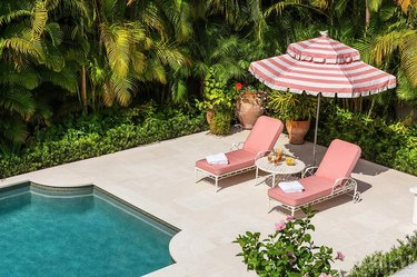 art deco decorating on a budget with lounge chairs and striped umbrella by pool