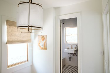 white ceramic wall-mounted sink with gold faucet, black and white hexagon tile floor, hanging pendant light fixture, window with tan Roman shade
