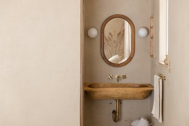 wood wall-mounted sink, oblong mirror with wood trim, two white round light sconces, towel bar with pink towel