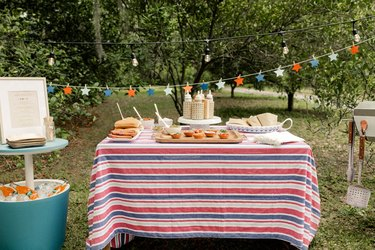 Gourmet hot dog bar with red, white and blue star garland, striped tablecloth and beverage cooler table with framed menu
