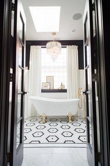 art deco decorating on a budget with clawfoot bathtub in black and white bathroom