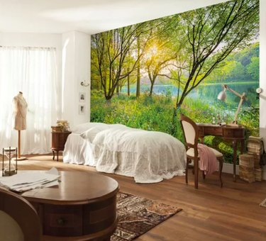 Bedroom with trees and water wallpaper with withe bed and desk