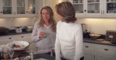 two women in kitchen with white cabinets