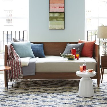 daybed in the living room idea with a midcentury wooden daybed with solid throw pillows and a small white table