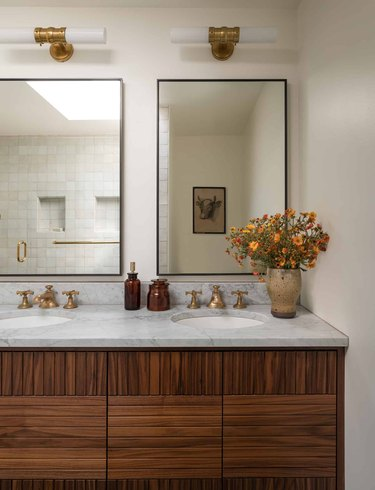 beige color bathroom with wood and marble double vanity and glass mirrors