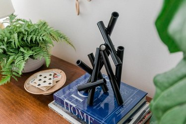 Black modern sculpture on books.