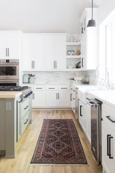 kitchen cabinet hardware idea with sage green island and wood flooring topped with area rug