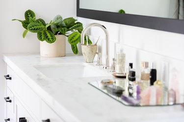 white bathroom vanity with quartz counters, white ceramic sink, silver faucet, glass tray with various beauty products, vase with green plant, rectangular mirror