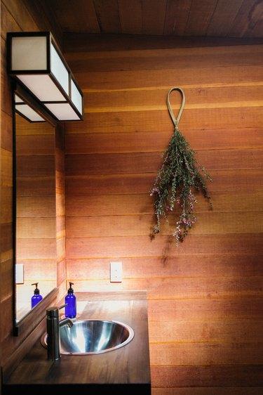 wood panel walls, wood bathroom countertop, stainless steel sink, rectangular mirror, hanging greenery