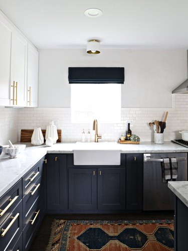 Modern and vintage kitchen cabinet hardware idea with brass pulls and farmhouse sink and marble countertop