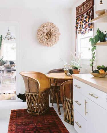 Kitchen nook idea with Mexican equipale chairs at a wooden table in a breakfast nook. A red vintage runner is in the foreground.