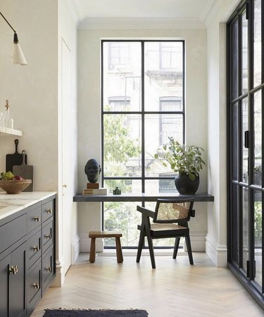 Kitchen nook idea with galley kitchen with black cabinets, marble countertops, a floor-to-ceiling window at one end, and a built-in desk at the window.