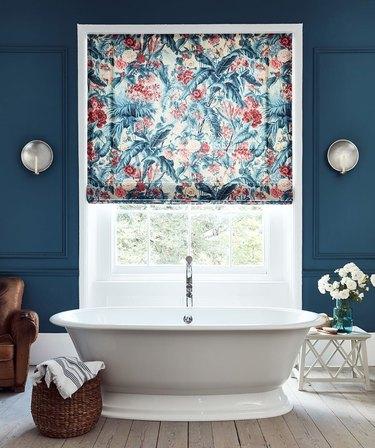 traditional bathroom idea with regal blue walls, floral drapes, metallic sconces