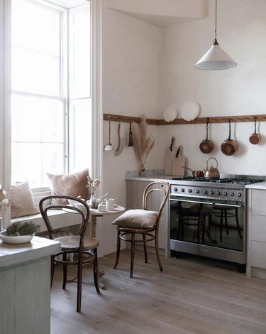 Kitchen nook idea with minimailst kitchen with a professional range, and a tiny bistro table and two vintage bentwood chairs by the window