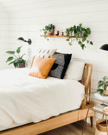 Bedroom shelving idea with houseplants and wood frame headboard