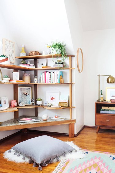 Bedroom shelving idea with corner unit filled with decorative items