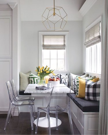 Kitchen nook idea with three clear acrylic chairs at a marble table in a breakfast nook in a white kitchen