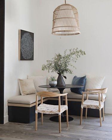 Kitchen nook idea with black tulip table in a corner nook with a neutral banquette and chairs