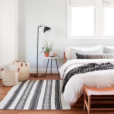 masculine boho bedroom with modern floor lamp and patterned textiles