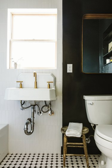 black and white apartment bathroom idea with mirror and stool near toilet