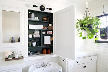 white pedestal sink, white vanity countertop, white recessed medicine cabinet with green interior, hanging plant, white subway tile wall