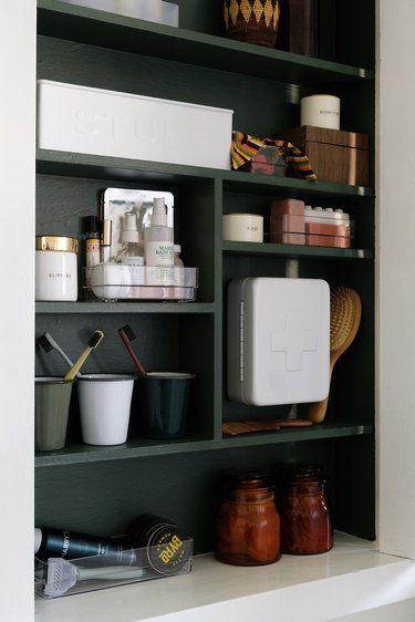 recessed medicine cabinet with green interior, beauty and medicinal products stored inside