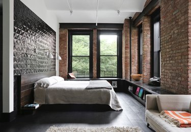 black and white bedroom idea with exposed brick and dark wood flooring