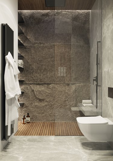 spa bathroom ideas with luxurious shower featuring stone wall and white fluffy bathrobes on a towel warmer