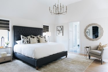 black and white bedroom idea with traditional accents and upholstered headboard
