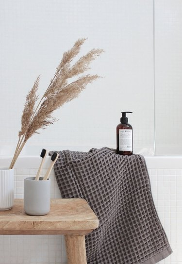 spa bathroom ideas in all white bathroom with natural wooden stool next to bathtub and gray waffle cotton towel