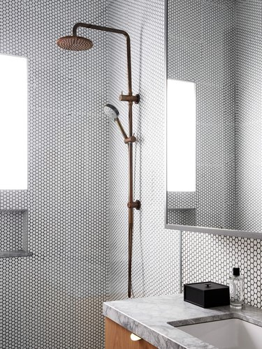 spa bathroom ideas with brass rainfall showerhead in an open shower with white penny tile