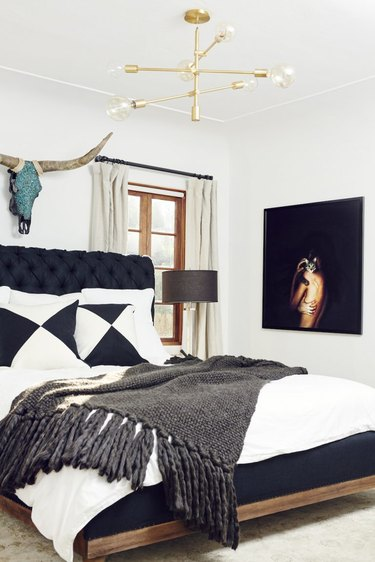 black and white bedroom idea with upholstered headboard and brass chandelier