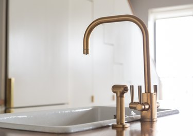 drop-in cast iron sink next to a gold faucet