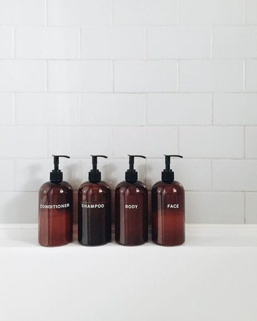 spa bathroom ideas featuring four amber-colored product dispensers lined up along a bathtub with white tile