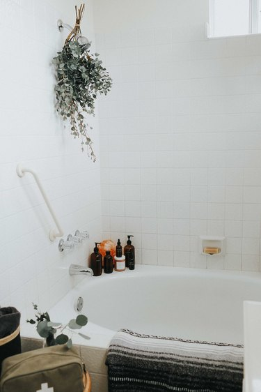 spa bathroom ideas with bundle of dried eucalyptus hanging from the showerhead
