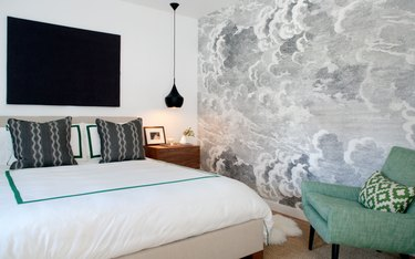 black and white bedroom idea with gray accent wall and hanging pendant light